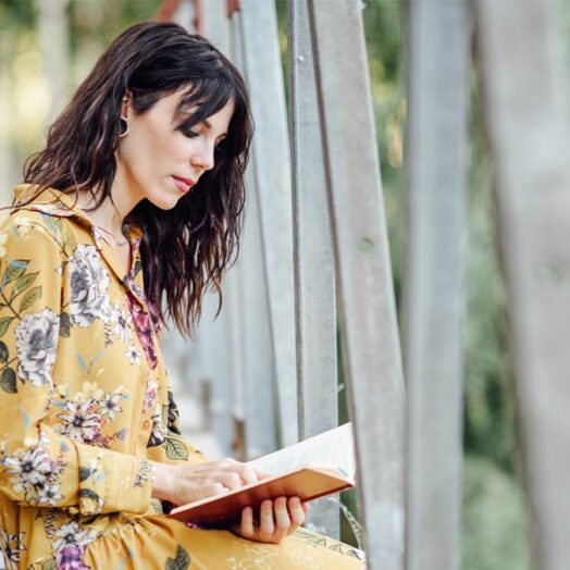 girl-reading-financial-advice-from-book-at-lake