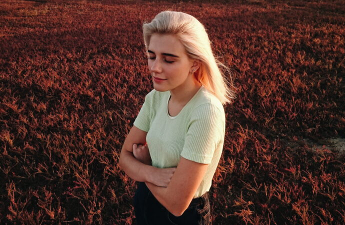 outdoors-grass-red-young-woman-crossed-arms-blond-girl-red-grass